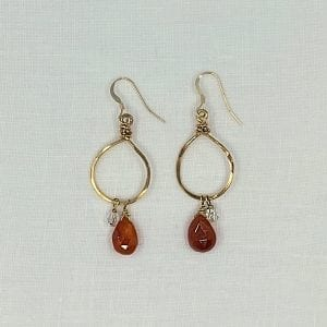 "Carnelian and Small Crystal Dangle Hoops. Briolette carnelian is paired with a small crsyatl bead on an oval hoop. 2"" long on hand forged gold filled wire with shepards hook."