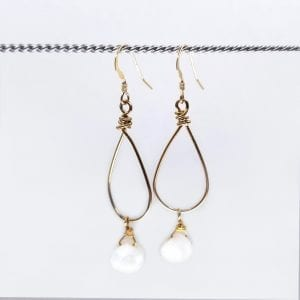 White Druzy Quartz hand from oval hoop earrings. Hand wrapped gold filled wire