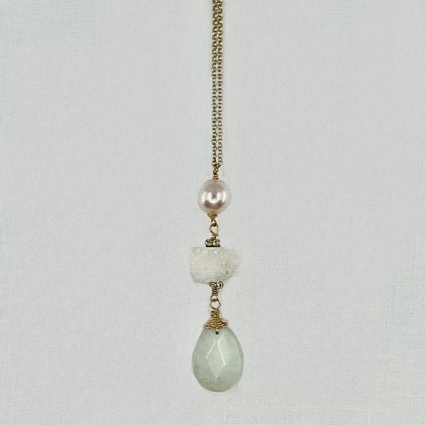 Three stone drop necklace feature a baroque pearl