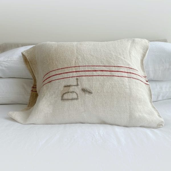 """A vintage grain sack made from linen and hemp. Natural in color, three red horizontal stripes are running the length and the initials D. L. written on it. Measurements: 29"""" long x 22"""" high."""