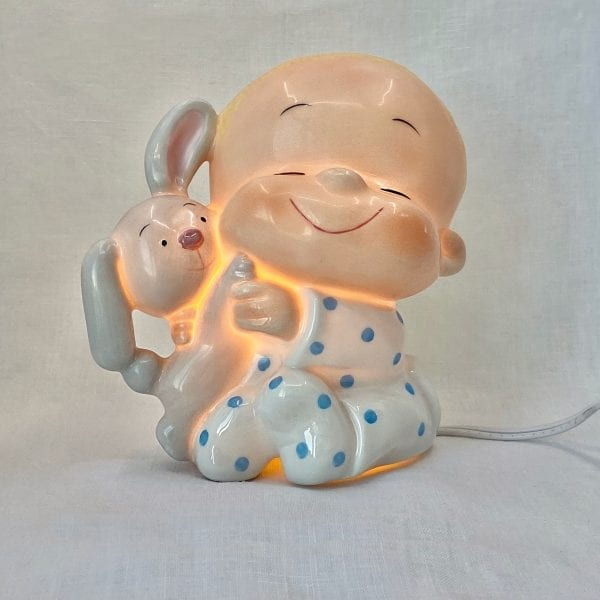 "Smiling infant wearing a onesie in white with blue polka dots. Infant is holding a smiling grey stuffed bunny. The entire night-light lights up and is made from ceramic. It has a makers mark of ""Marty Links"" on the back."