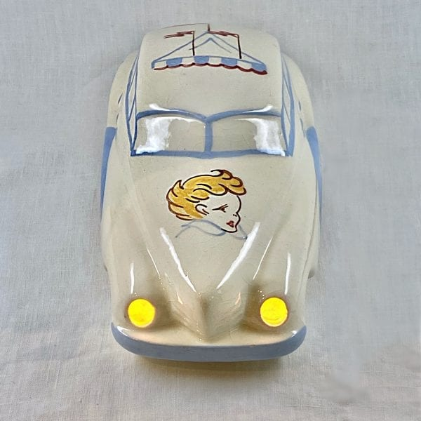Cream colored vintage car night-light painted with blue trim on the windows and side panel. The roof is painted wth a circus tent top and hood is painted with a young boys head. When lit, the ceramic car's headlights glow.