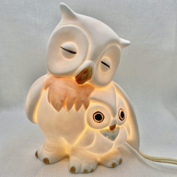 Sleeping mama owl has her wing covering her owlet who is wide awake. Night-light is made from a matte finish ceramic.