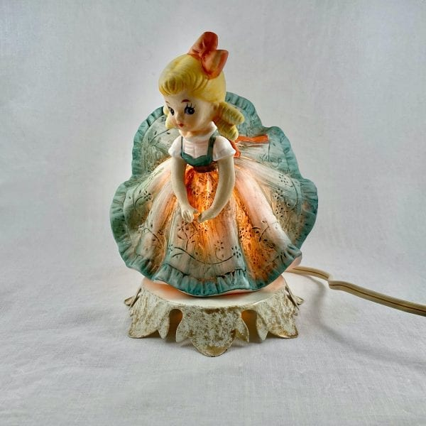 Blonde girl with a red bow in her hair and in an engraved floral green dress leans forward as the back of her dress is blown upward, exposing her bottom. Made of ceramic the entire night-light glows and has a sticker on the base with the name Aladdin Giftware.