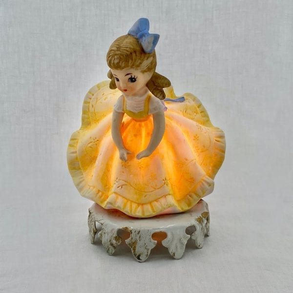 Brunette girl with a blue bow in her hair and in an engraved floral blue dress leans forward as the back of her dress is blown upward, exposing her bottom. Made of ceramic, the entire night-light glows and has a sticker on the base with the name Aladdin Giftware.