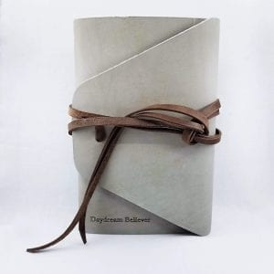 "Leather journal with double wrap tie closure. Comes with 160 blank pages. Embossed ""Daydream Believer"". Size 6.25"" x 9"". Color: Stone"