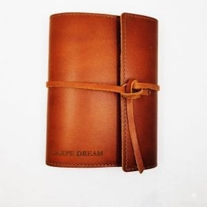 """Refillable leather journal with leather tie closure. Embossed: """"Carpe Dream"""". Size: 6.75"""" x 8.75"""". Color: Saddle"""