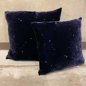 "Navy velvet throw pillow with a starburst pattern and multi-colored dots. Measures 24""x24""."