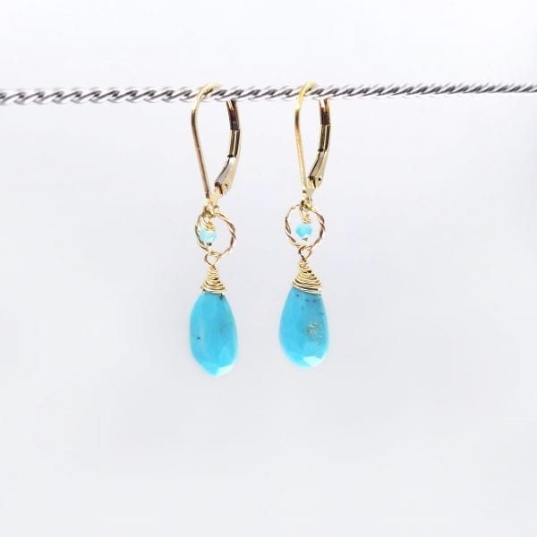 """Elongated teardrop sleeping beauty turquoise and apatite drop earrings are finished with a gold-filled, lever back closure. The earrings measure 1.25"""" long."""