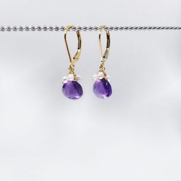 "Briolette cut amethyst, with a freshwater pearl cluster, earrings are finished with a gold-filled, lever back closure. The earrings measure 1.25"" long."