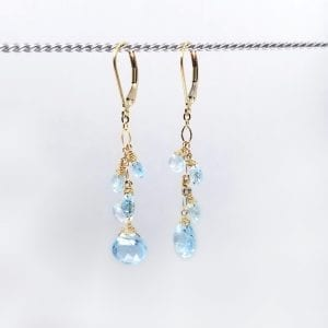 "Blue topaz graduated briolettes cascade from gold-filled, lever back closure earrings. The earrings measure 2"" long."