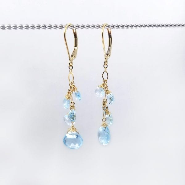 """Blue topaz graduated briolettes cascade from gold-filled, lever back closure earrings. The earrings measure 2"""" long."""