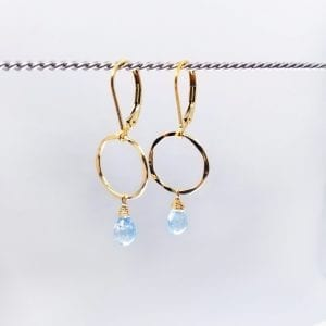 "Teardrop, briolette cut blue topaz are suspended from a small, hammered gold-filled circle. The earrings are 1.5"" long and have a lever back closure."