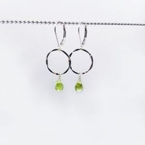 "Teardrop, briolette peridot are suspended from a small, hammered sterling silver circle. The earrings are 1.5"" long and have a lever back closure."