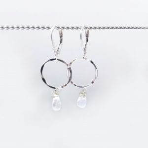 "Teardrop, briolette rainbow moonstone are suspended from a small, hammered sterling silver circle. The earrings are 1.5"" long and have a lever back closure."