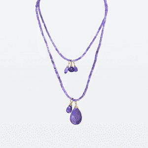 "A 30'' strand of amethyst beads with a cluster of floating iolite and tanzanite and a larger pear shaped amethyst centerpiece. Necklace has a 2"" extender chain."