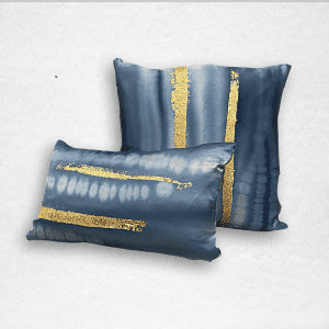 "Satin pillow is light blue with an ombre dye. Two stripes of gold leaf are hand applied to the design. Measures 20""x20""."