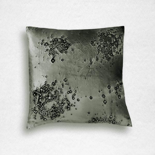 """Dark green velvet pillow is embossed with a mineral scatter print. Measures 20""""x20""""."""