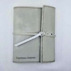 "Refillable leather journal with leather tie closure. Embossed: ""Daydream Believer"". Size: 6.75"" x 8.75"". Color: Stone"