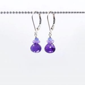 "Amethyst briolettes are topped with a cluster of chalcedony and are finished with gold-filled, lever back closure. The earrings measure 1.25"" long."