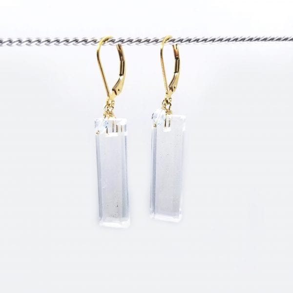 "Elongated rectangular cut quartz are topped with aquamarine beads and finished with gold-filled, lever back closures. The earrings measure 2"" long."
